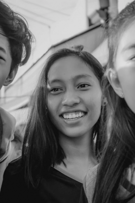 A group of young people smiling in the direction of the camera.
